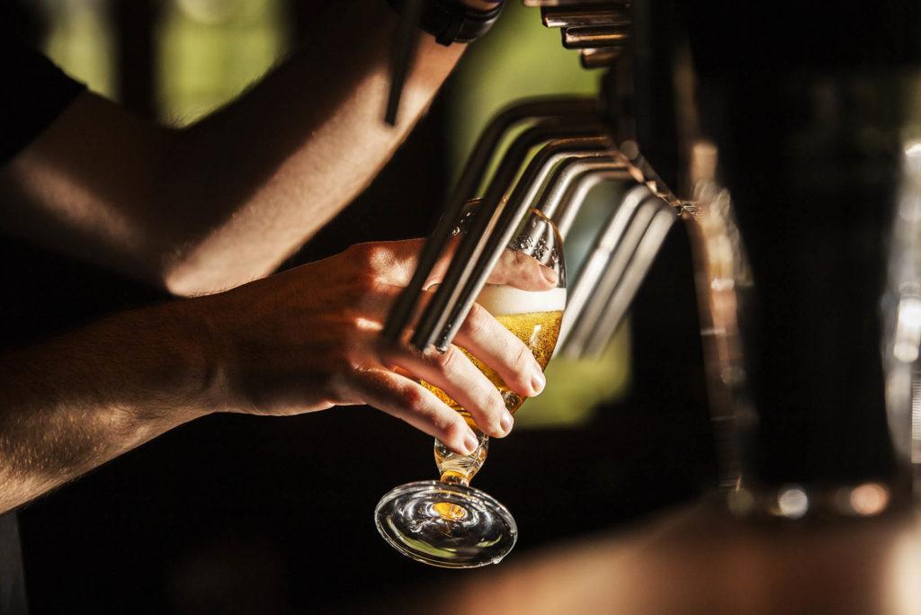 Barman dans un bar avec un verre de bière